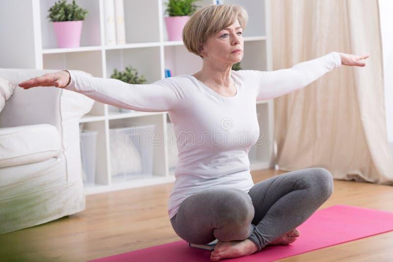 Yoga practicante de la mujer en casa imagenes de archivo