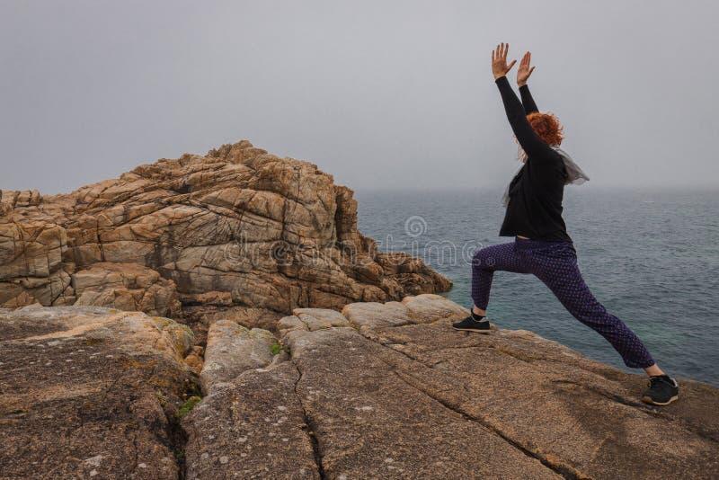 Yoga practicante de la mujer en la costa de la armadura foto de archivo