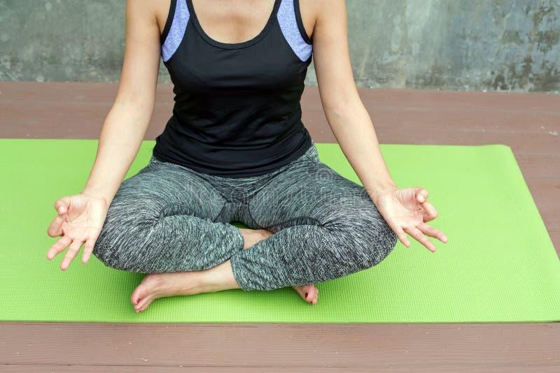 yoga practicante de la mujer en la estera verde en fondo urbano/de la pared imagen de archivo