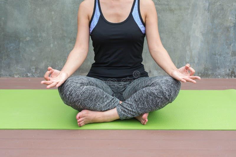 yoga practicante de la mujer en fondo urbano/de la pared imagen de archivo
