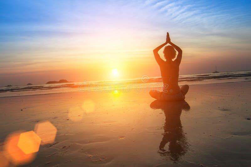 Yoga practicante de la mujer en la costa durante puesta del sol Relájese imagenes de archivo