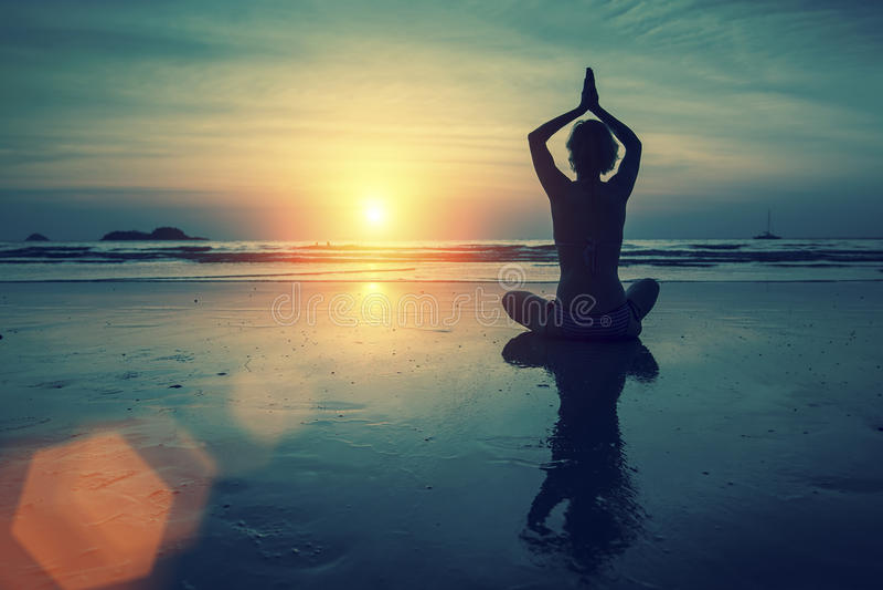 Yoga practicante de la mujer en la posición de Lotus en la puesta del sol respecto a la costa de mar fotos de archivo libres de regalías