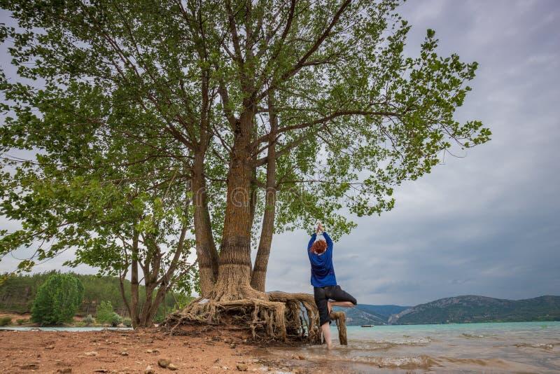 Yoga practicante de la mujer en la orilla de un lago foto de archivo libre de regalías