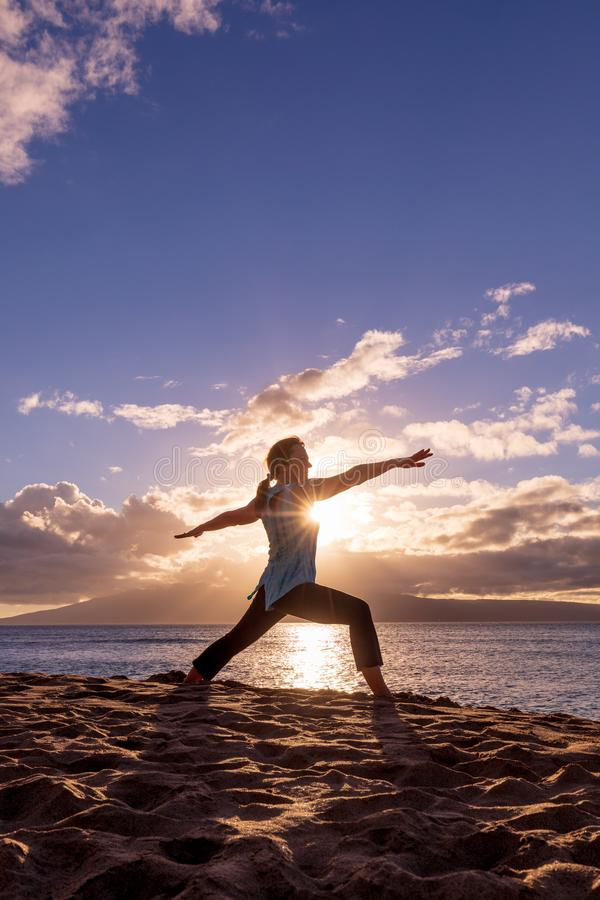 Yoga practicante de la mujer en una playa de Maui en la puesta del sol foto de archivo