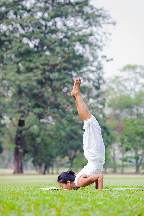 Yoga practicante de la mujer hermosa en el parque fotografía de archivo