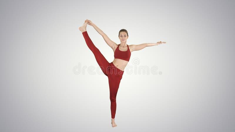 Yoga practicante de la mujer joven, colocándose en el ejercicio de Utthita Hasta Padangustasana, mano extendida a la actitud del  fotos de archivo libres de regalías