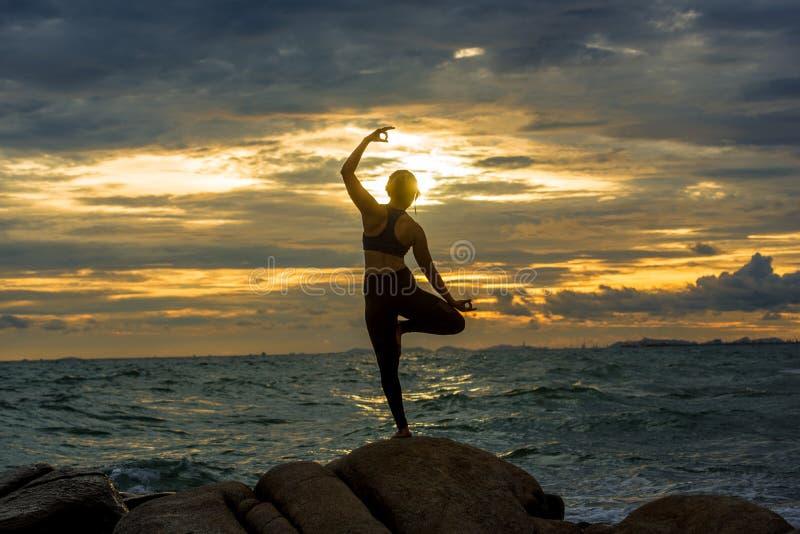 Yoga practicante de la mujer joven en una roca en el mar imagenes de archivo