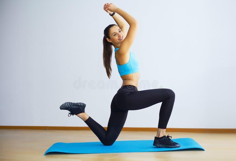 Yoga practicante de la mujer joven, haciendo cosa salvaje, ejercicio del Tirón--perro foto de archivo libre de regalías