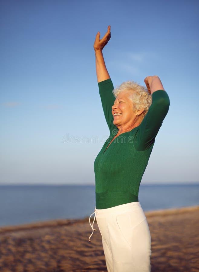 Yoga practicante de la mujer madura apta en la playa imagen de archivo