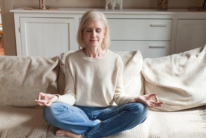 Yoga practicante de la mujer mayor tranquila que reflexiona sobre el sofá fotos de archivo