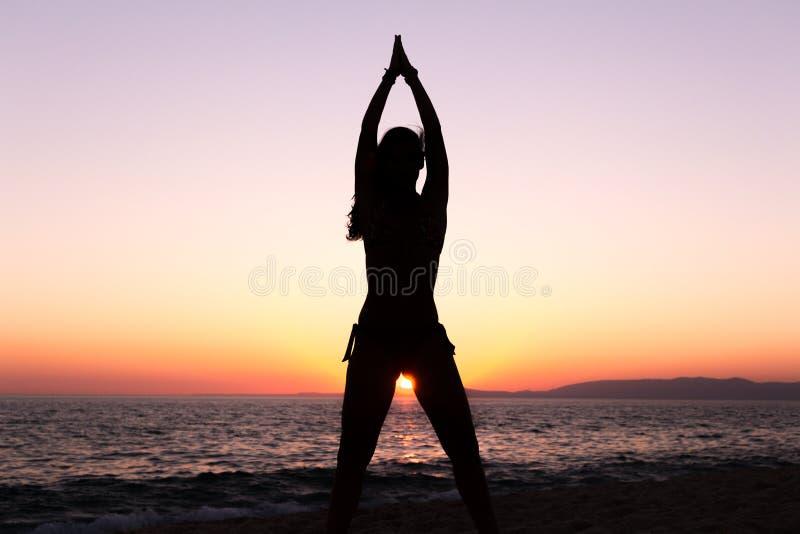 Yoga practicante de la mujer, puesta del sol en la playa imagen de archivo