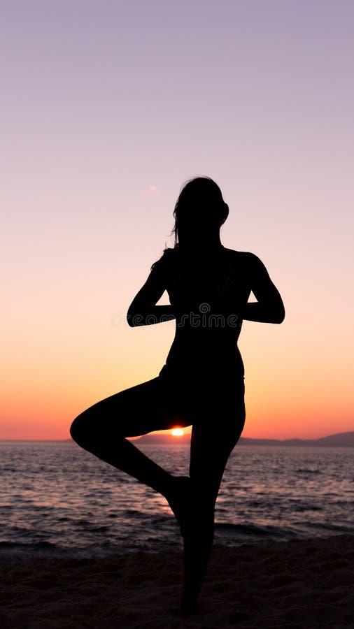 Yoga practicante de la mujer, puesta del sol en la playa foto de archivo libre de regalías