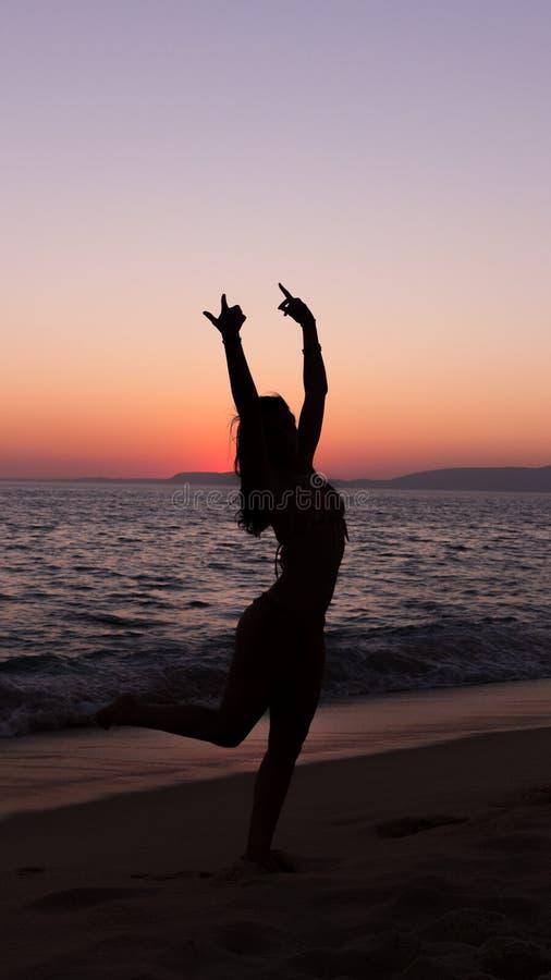 Yoga practicante de la mujer, puesta del sol en la playa imagen de archivo libre de regalías