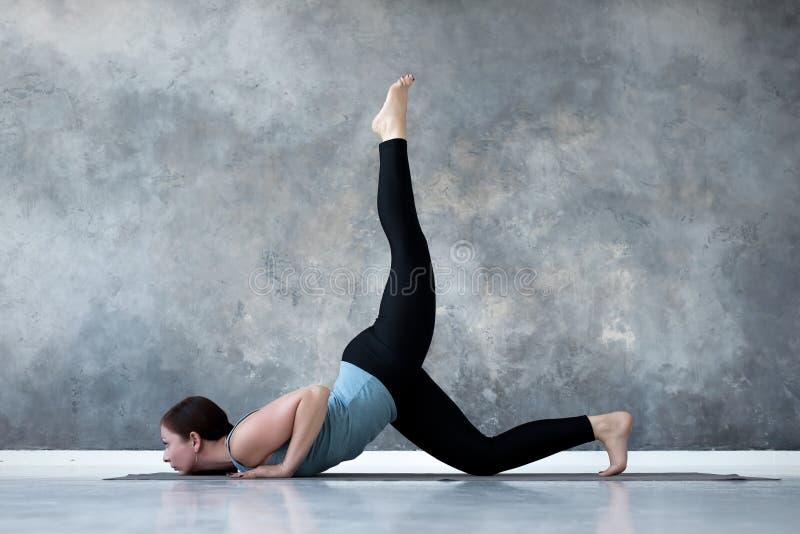 Yoga practicante de la mujer que hace el pada Shalabhasana, la variación del eka de la actitud de la langosta imagenes de archivo