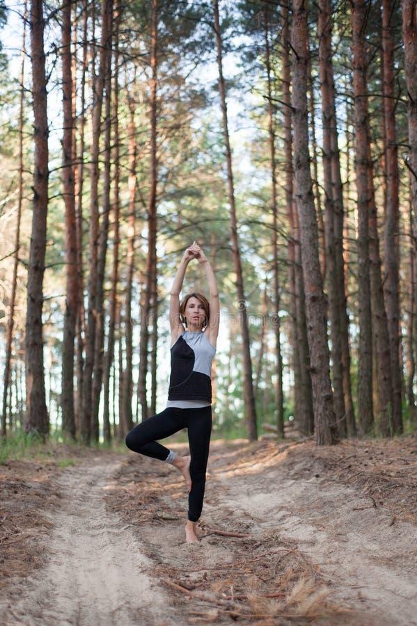 Yoga practicante de la mujer solamente en el bosque al aire libre imagenes de archivo