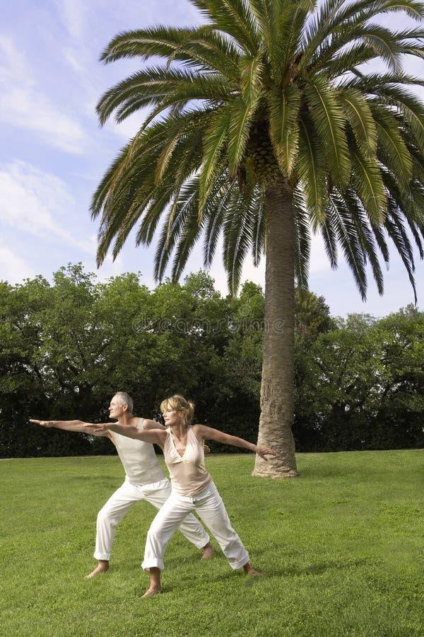 Yoga practicante de los pares en parque imagenes de archivo