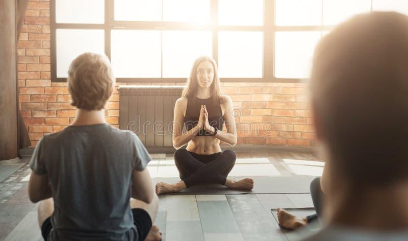 Yoga practicante del grupo de personas con el instructor fotos de archivo