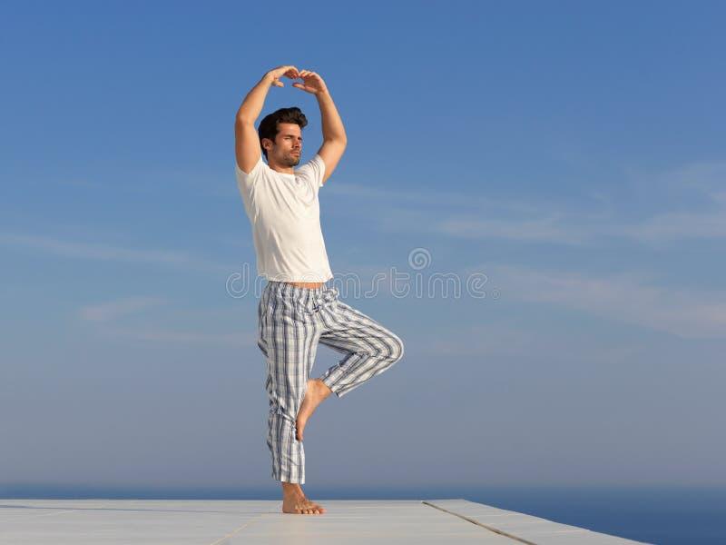 Yoga practicante del hombre joven imagenes de archivo