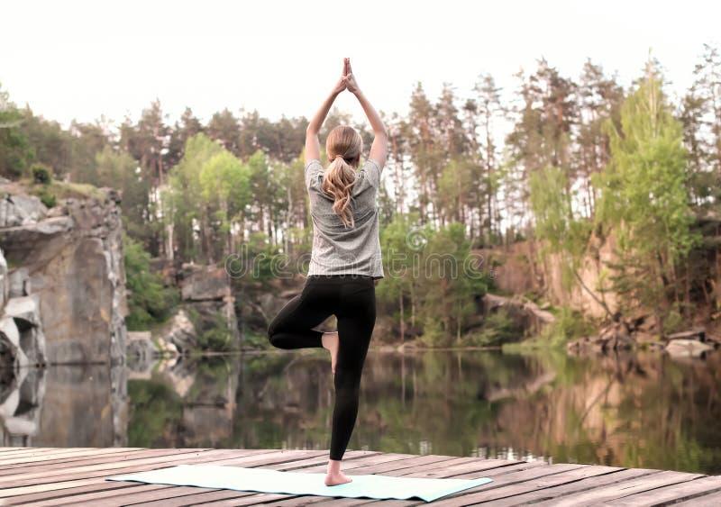Yoga practicante hermosa de la mujer joven al aire libre por mañana fotografía de archivo libre de regalías