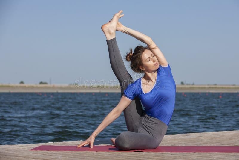 Yoga practicante hermosa de la mujer joven al aire libre por mañana imagen de archivo libre de regalías