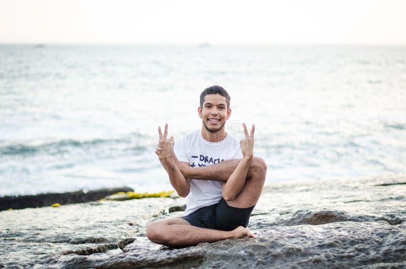 Yoga practicante peruana atractiva, aptitud o pilates del hombre joven en la playa, haciendo garbhasana foto de archivo libre de regalías