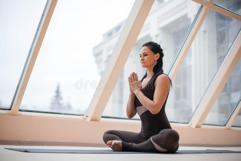 Yoga practicante sonriente atractiva joven de la mujer, sentándose en el medio ejercicio de Lotus en ventanas grandes del fronte, imágenes de archivo libres de regalías