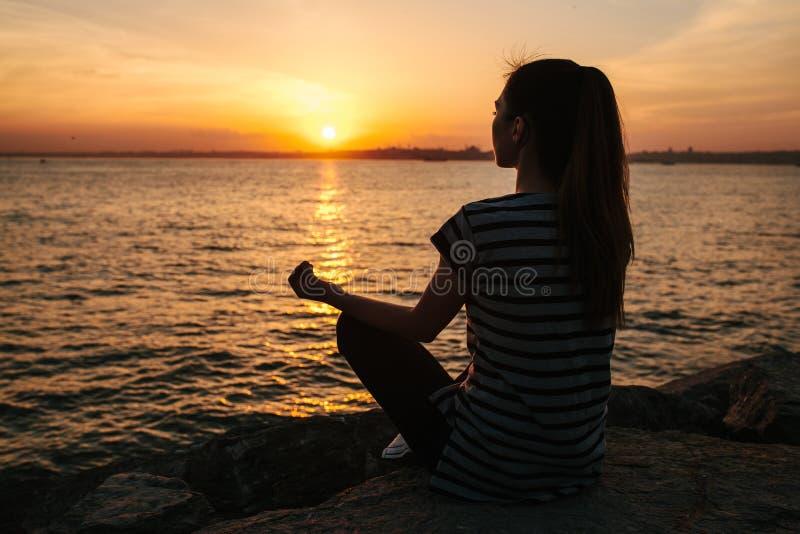 Yoga practicante y meditación de la muchacha hermosa joven en las rocas al lado del mar en la puesta del sol Deporte Yoga meditac fotos de archivo