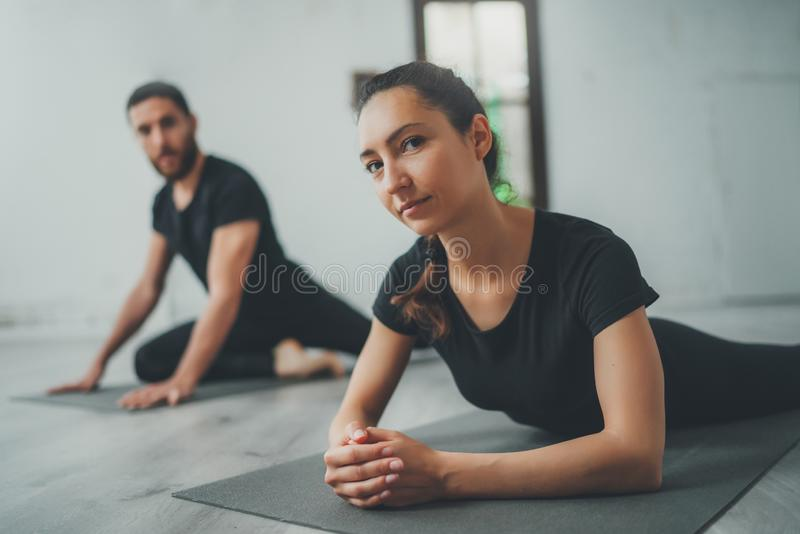 Yoga Practice Exercise Class Concept. Two beautiful people doing exercises.Young woman and man practicing yoga indoors. royalty free stock photos