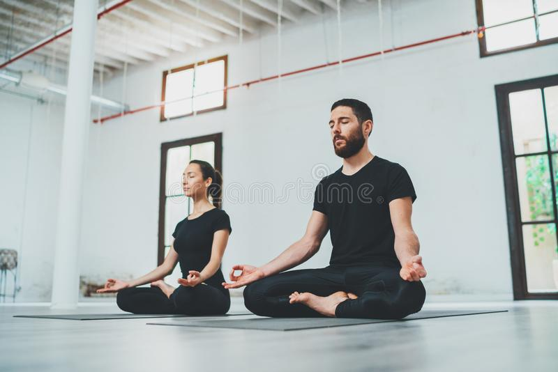 Yoga Practice Exercise Class Concept. Two beautiful people doing exercises.Young woman and man practicing yoga indoors. stock photography