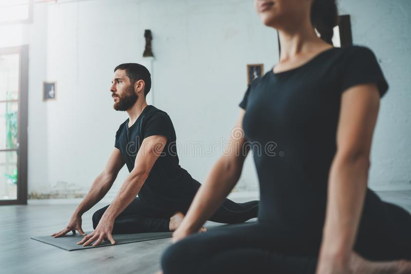Yoga Practice Exercise Class Concept. Two beautiful people doing exercises.Young woman and man practicing yoga indoors. stock photos