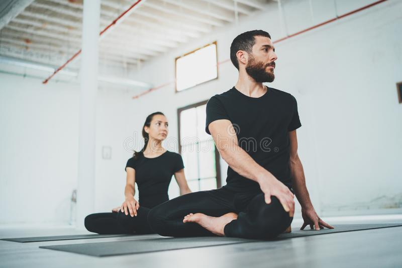 Yoga Practice Exercise Class Concept. Two beautiful people doing exercises.Young woman and man practicing yoga indoors. stock image