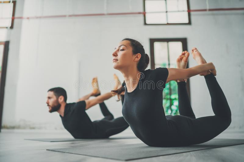 Yoga Practice Exercise Class Concept. Two beautiful people doing exercises.Young woman and man practicing yoga indoors. stock photo