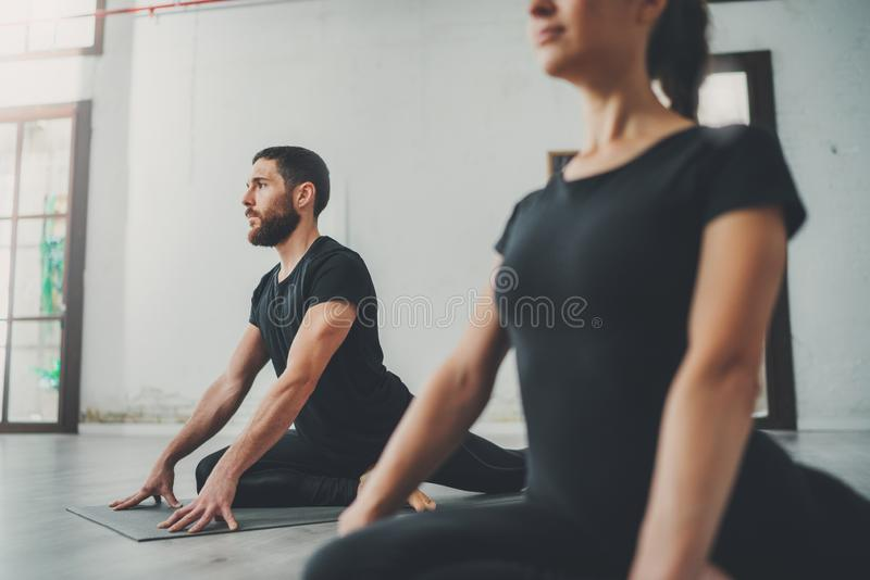 Yoga Practice Exercise Class Concept. Two beautiful people doing exercises.Young woman and man practicing yoga indoors. royalty free stock photo