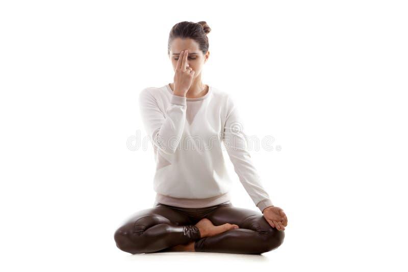 Yoga practice nadi shodhana pranayama. Yoga girl on white background practicing nadi shodhana pranayama (Alternate, Nostril, Breathing) in lotus pose stock photos