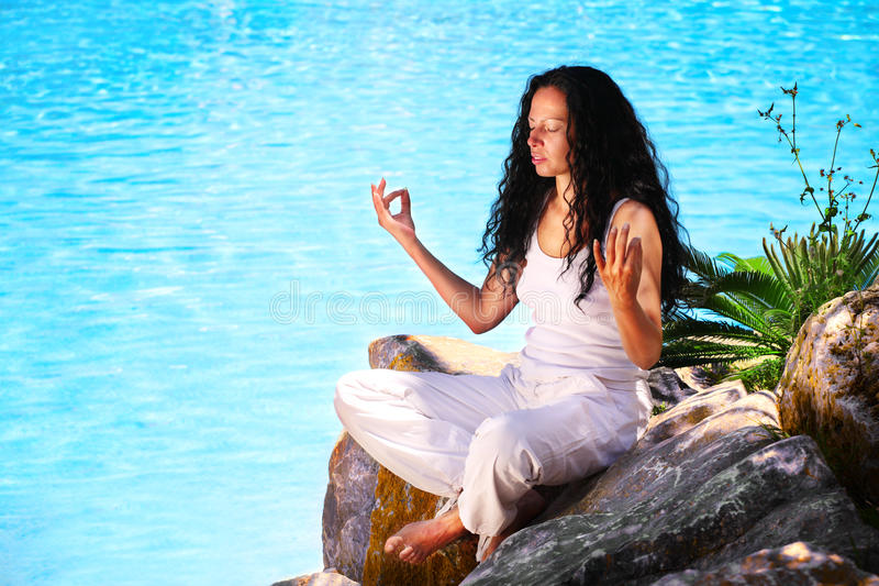 Yoga practise. Beautiful young woman doing yoga exercise in tropical setting royalty free stock image