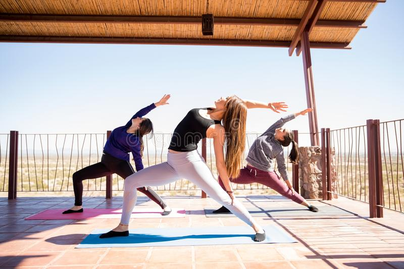 Yoga practise at fitness class. Three hispanic women standing and stretching backward in reverse warrior pose at yoga class royalty free stock images