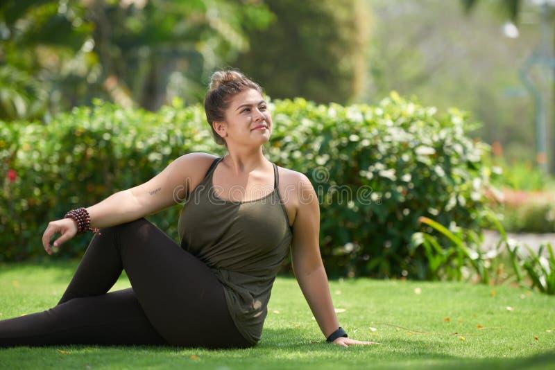 Yoga practise. Pretty smiling woman enjoying yoga practice in local park stock photo