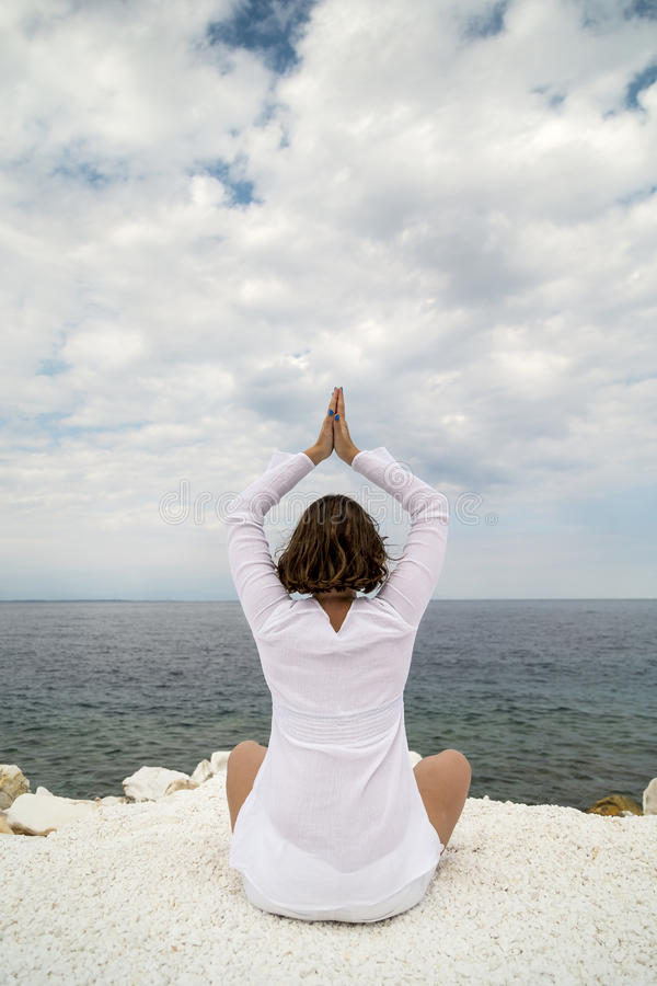 Yoga practise. Young woman practicing yoga near marble beach on Thassos island, Greece on a cloudy summer day royalty free stock photos