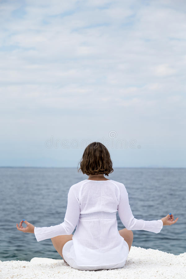 Yoga practise. Young woman practicing yoga near marble beach on Thassos island, Greece on a cloudy summer day stock image