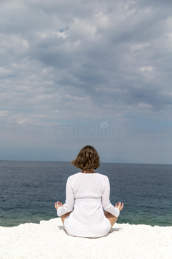 Yoga practise. Young woman practicing yoga near marble beach on Thassos island, Greece on a cloudy summer day royalty free stock photo