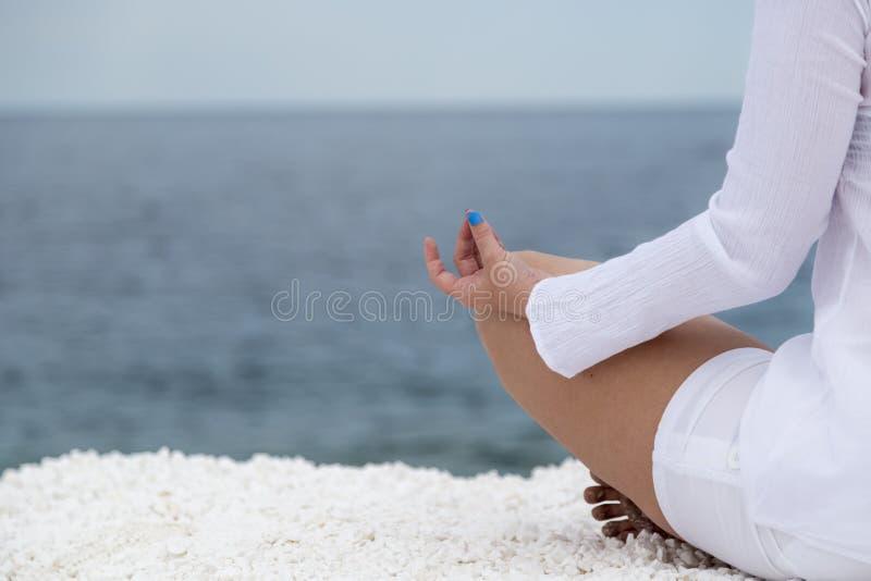 Yoga practise. Young woman practising yoga near marble beach on Thassos island, Greece royalty free stock photos