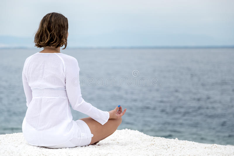 Yoga practise. Young woman practising yoga near marble beach on Thassos island, Greece royalty free stock images
