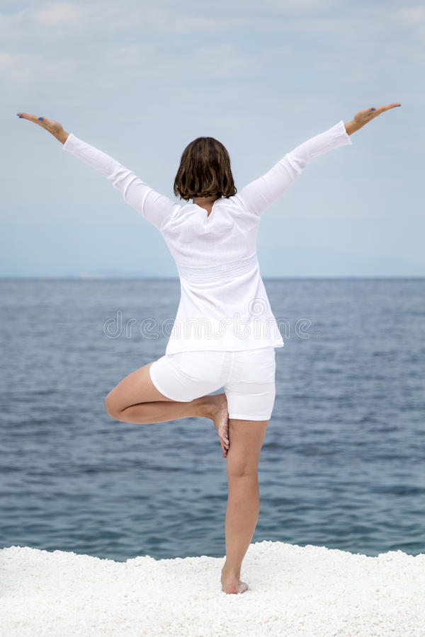 Yoga practise. Young woman practising yoga near marble beach on Thassos island, Greece stock photography
