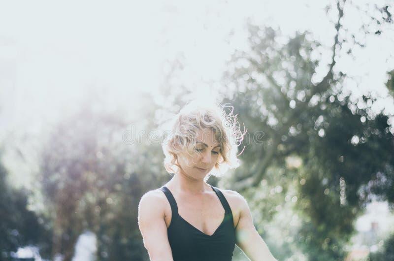 Yoga que medita y practicante de la mujer, Padmasana Meditación en Sunny Autumn Day At Park Entrenamiento al aire libre foto de archivo