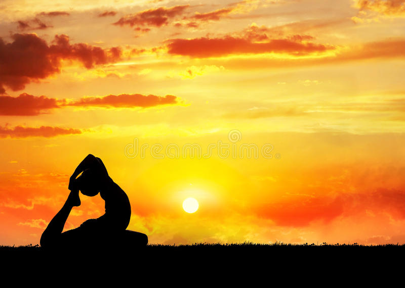 Yoga raja kapotasana pigeon pose. By man silhouette at sunset sky background. Free space for text and can be used as template for web-site stock image