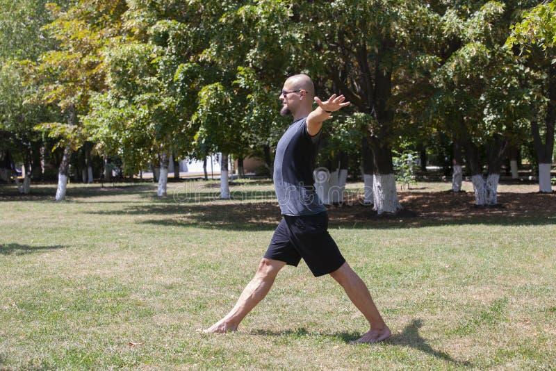 Yoga s'exer?ant de jeune homme dehors Le type sportif fait ?tirer l'exercice sur un tapis bleu de yoga, sur l'au sol de sports images stock