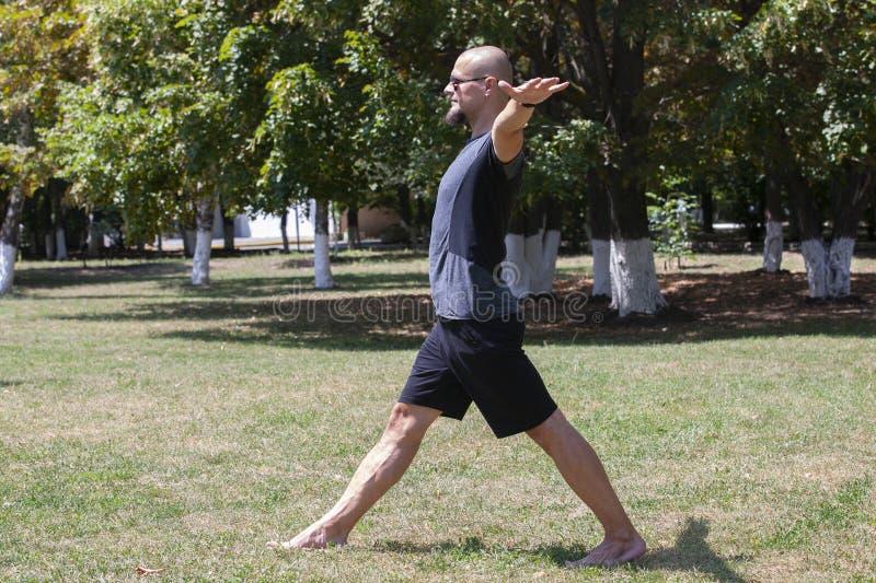 Yoga s'exer?ant de jeune homme dehors Le type sportif fait ?tirer l'exercice sur un tapis bleu de yoga, sur l'au sol de sports images libres de droits
