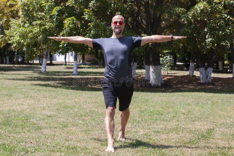 Yoga s'exer?ant de jeune homme dehors Le type sportif fait ?tirer l'exercice sur un tapis bleu de yoga, sur l'au sol de sports image libre de droits