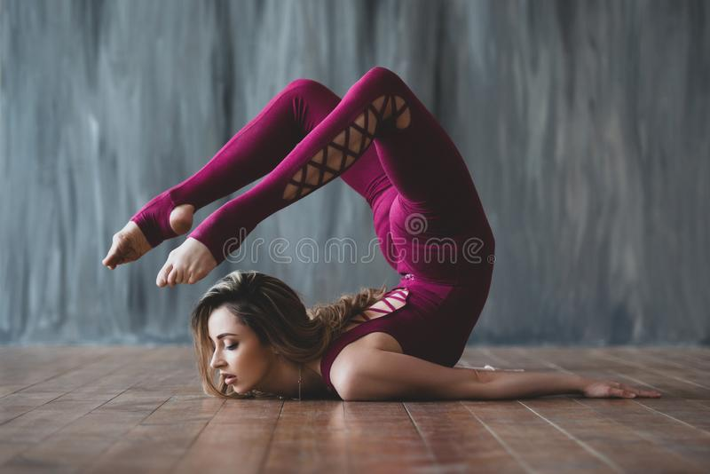 Yoga scorpion pose. Fit sporty girl is stretching. Young beautiful gymnast woman in a jumpsuit doing gymnastic exercises royalty free stock photography