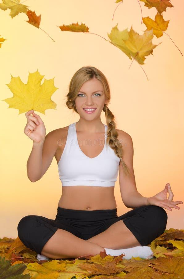 Yoga se reposant de sourire de pratique en matière de femme sous des feuilles photographie stock libre de droits